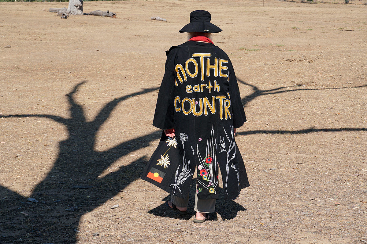 Film still from 'Mother's Little Helpers' by Karla Dickens,  featuring Bruce Pascoe, wearing a jacket emblazoned with the words Mother Earth Country.