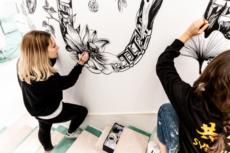 Two people painting a mural in a stairwell